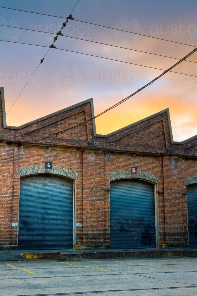 Industrial rail shed with warehouse roller doors during sunrise - Australian Stock Image