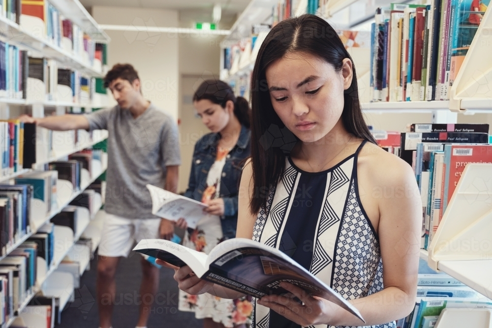 International student reading book in university library - Australian Stock Image