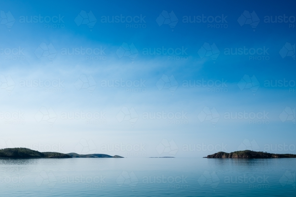 Islands in the distance through glassed off water in remote location - Australian Stock Image