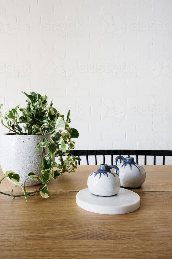 Ivy pot plant on table and white brick wall in dining room vertical - Australian Stock Image