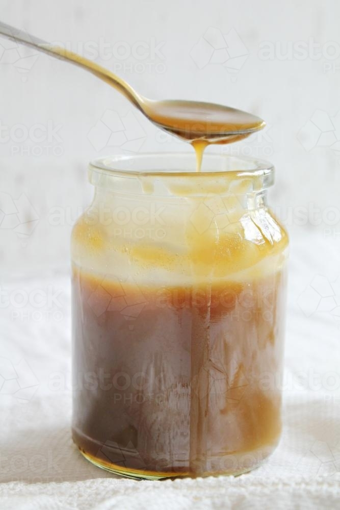 Jar of caramel sauce with spoon dripping - Australian Stock Image
