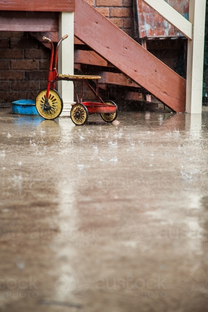 Kids bikes and toys left outside in the rain - Australian Stock Image