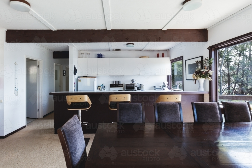 Kitchen and dining area of older style retro funky Australian beach house - Australian Stock Image