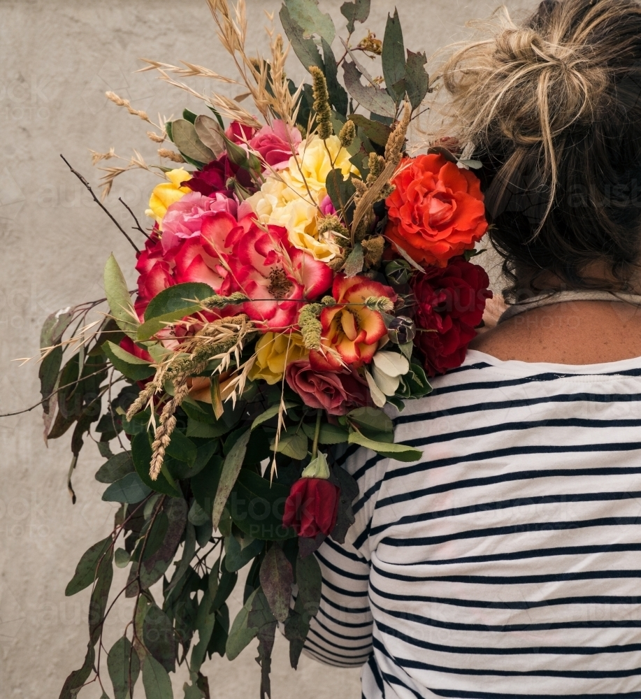 Image Of Lady Florist Holding Big Bunch Of Flowers Over Her Shoulder