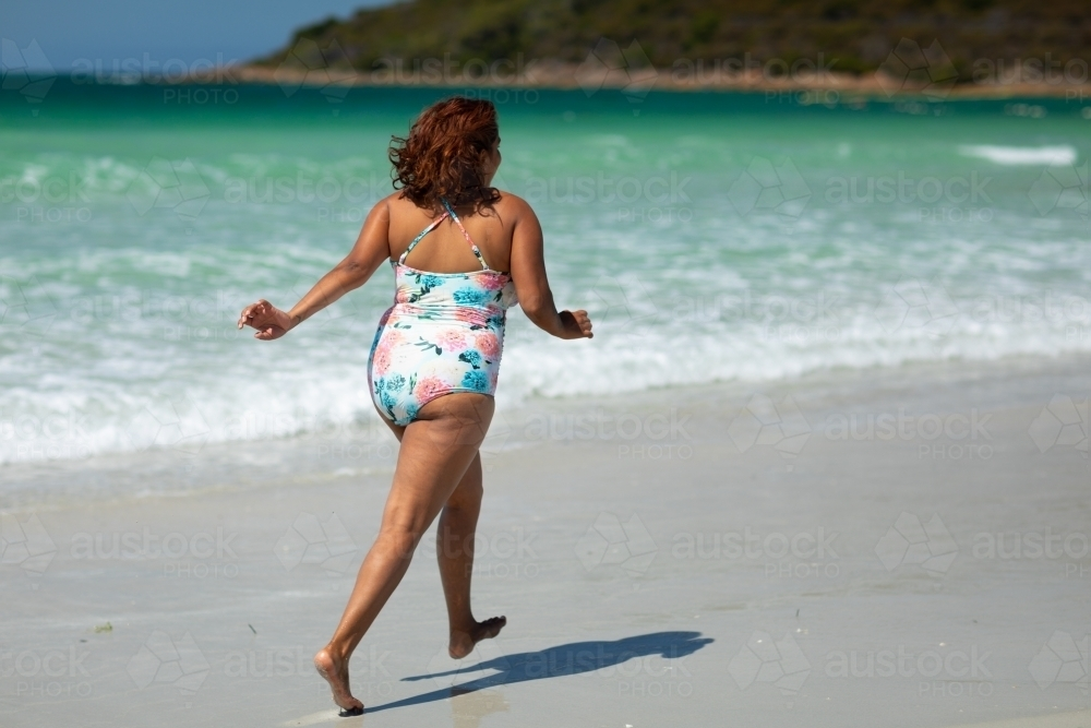 lady running along sea shore wearing swimming costume - Australian Stock Image