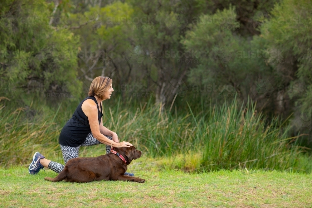 lady with chocolate Labrador lying down in green parkland - Australian Stock Image