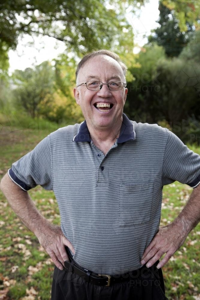 Laughing man with disability standing outside with hands on hips - Australian Stock Image