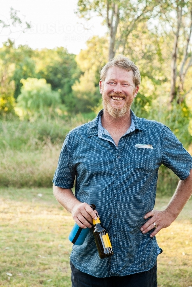 Laughing man with two beer bottles in the park - Australian Stock Image