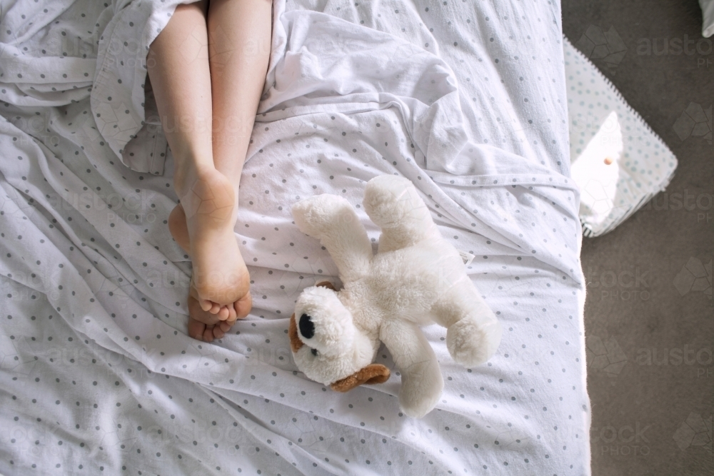 Legs and feet of a child laying in a messy bed with a teddy - Australian Stock Image