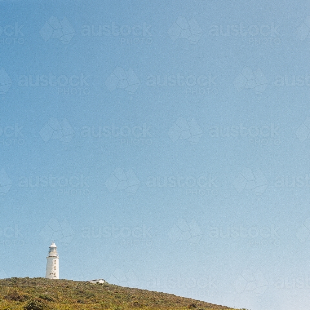 Lighthouse in the distance on a headland with blue sky background - Australian Stock Image