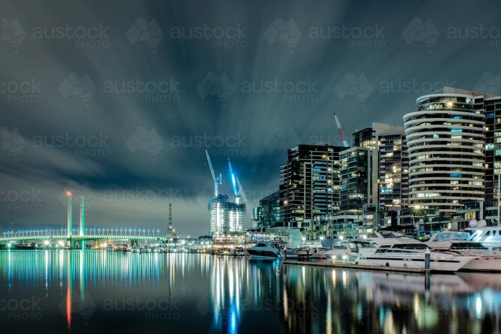Lights of docklands and Bolte Bridge reflected in water at night - Australian Stock Image