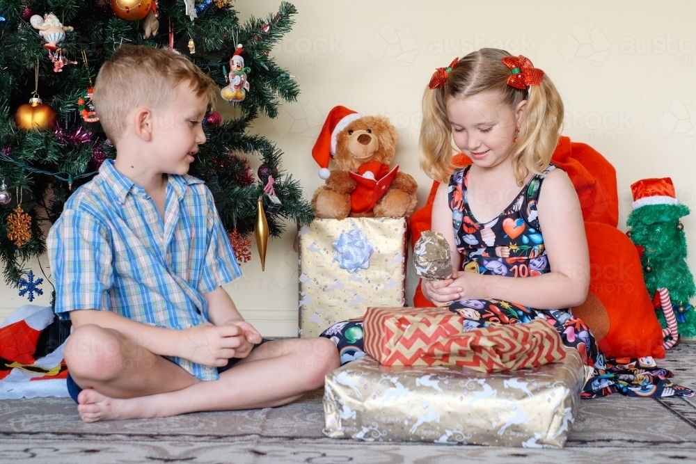 Little boy giving his sister a gift on Christmas day - Australian Stock Image