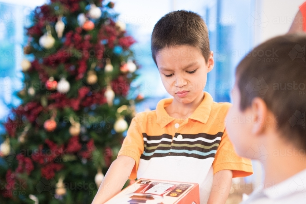little boy opening christmas presents at home australian stock image