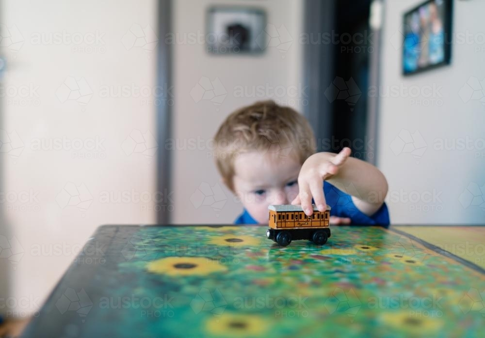 Little Boy playing with a Toy Train - Australian Stock Image