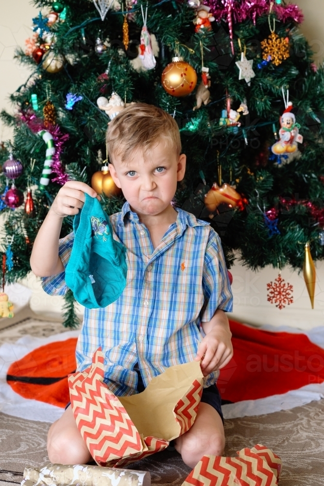 Little boy unhappy with a gift he has opened on Christmas day next to the Christmas tree - Australian Stock Image