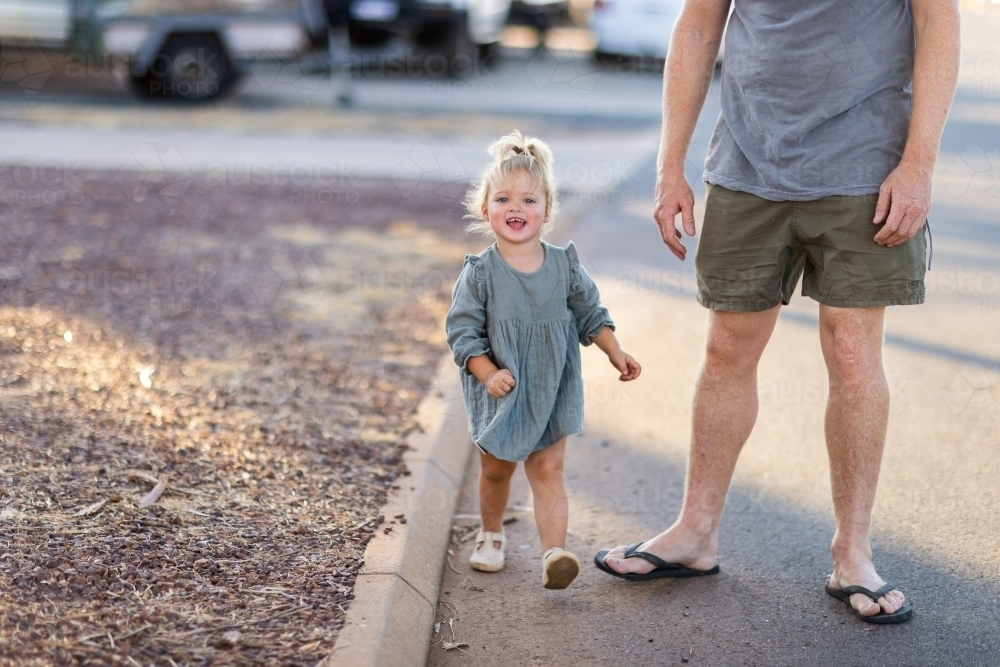 little girl boldly stepping out with dad along edge of road - Australian Stock Image