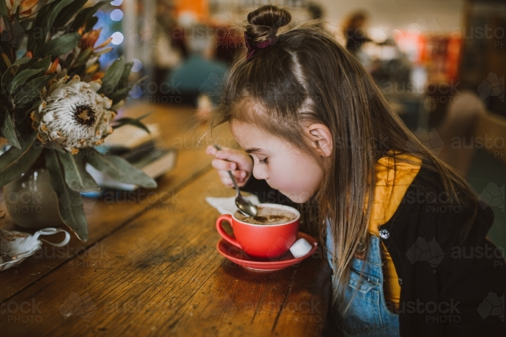 Little girl drinking a hot chocolate - Australian Stock Image