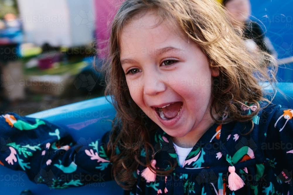 Little girl filled with joy on spinning ride - Australian Stock Image