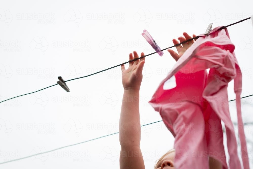 Little girl hanging clothes on the line - Australian Stock Image