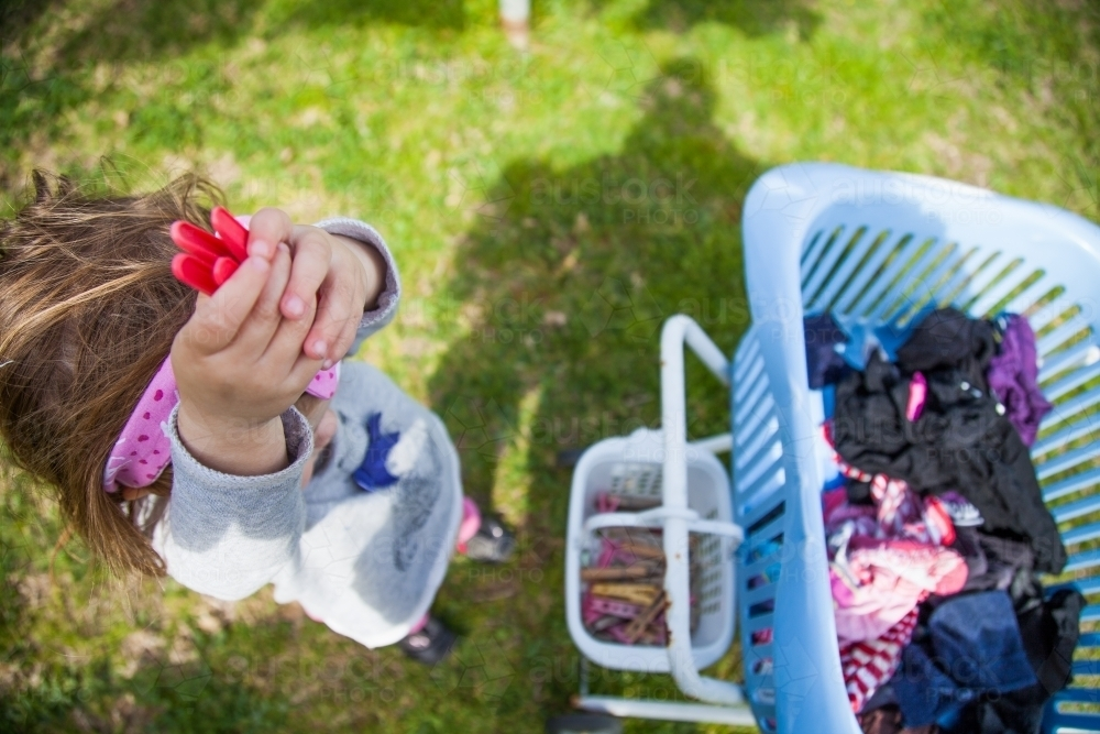 Little girl helping with washing by handing pegs up - Australian Stock Image