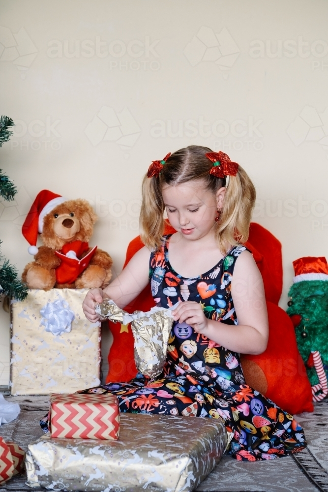 Little girl in an emoji dress opening a Christmas present - Australian Stock Image