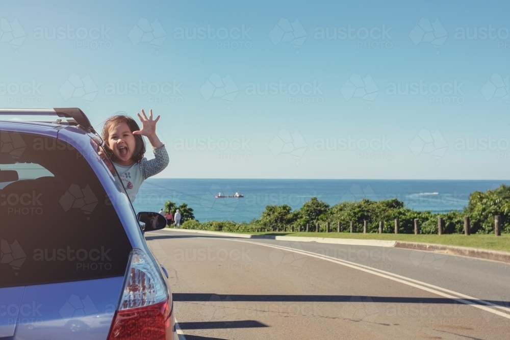 Little girl in the car on roadside with ocean background - Australian Stock Image