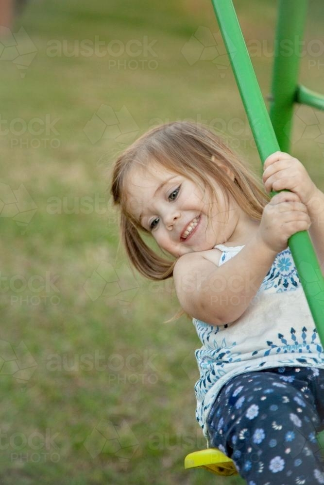 Little girl playing on the swings in the backyard - Australian Stock Image