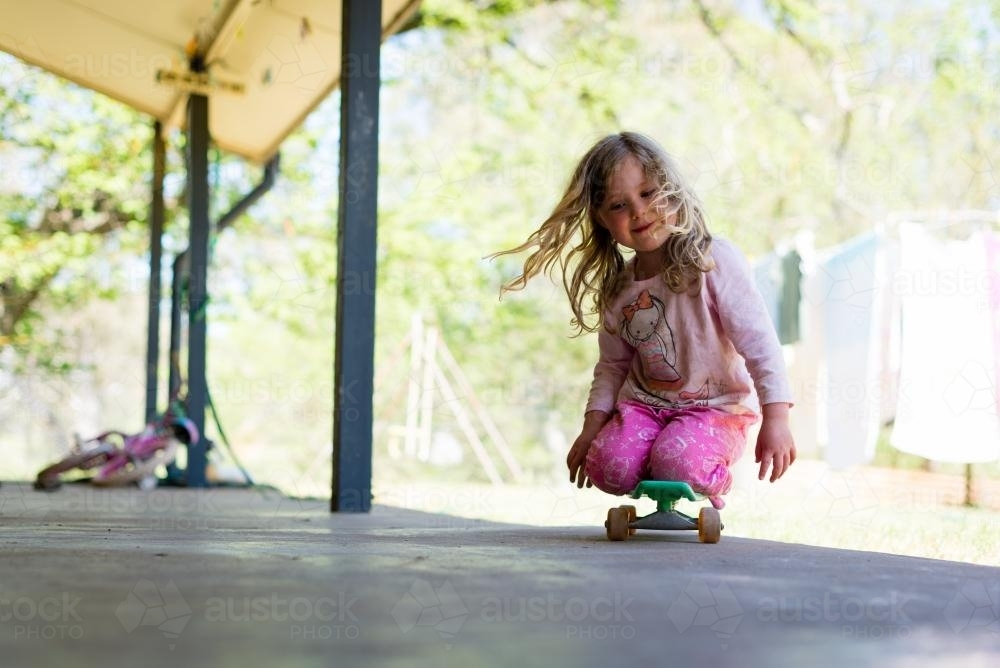 Little girl riding her skateboard - Australian Stock Image