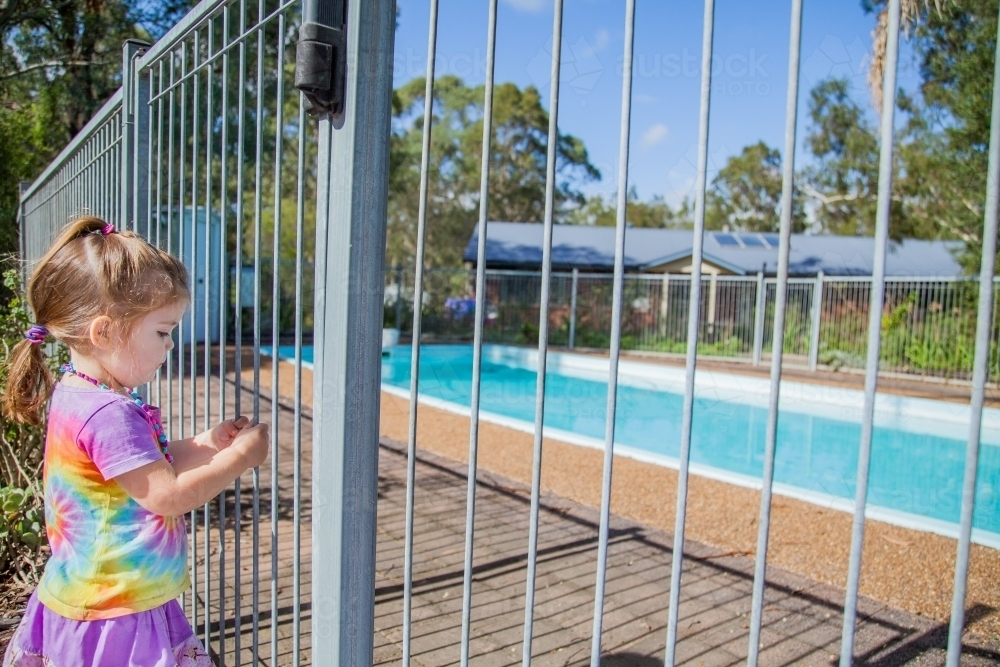 Little girl standing safely outside pool fence gate looking in - Australian Stock Image