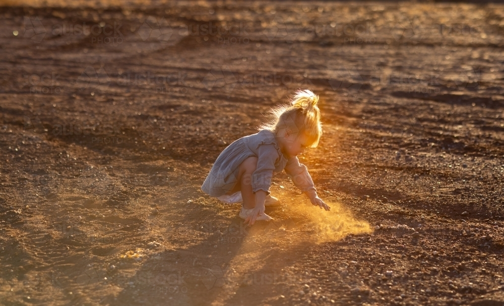 little kid playing in the dirt with backlight highlighting dust - Australian Stock Image