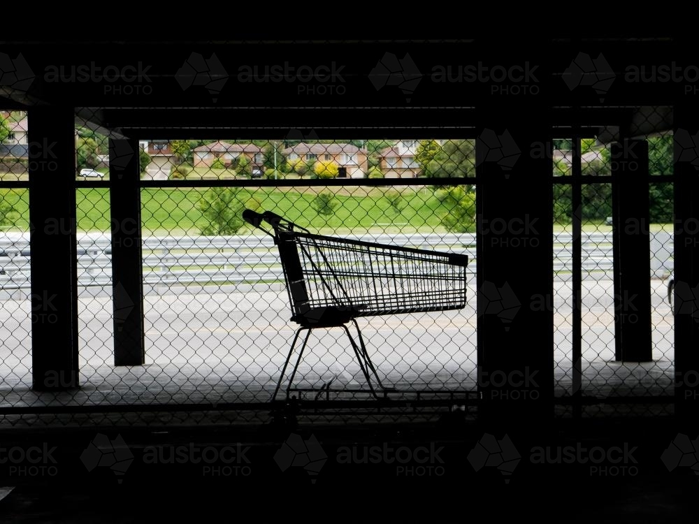 Lone shopping trolley in dark supermarket parking area - Australian Stock Image