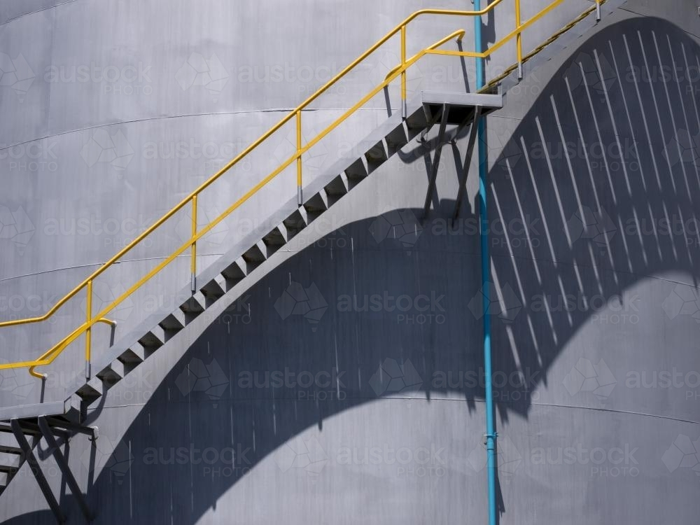 Long shadows of stairs going up a circular tank - Australian Stock Image