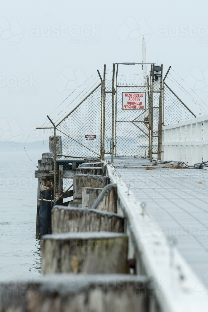 Looking along a seaside jetty to a locked gate and exclusion fencing - Australian Stock Image