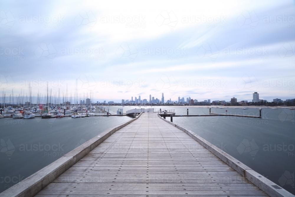 Looking along jetty to moored boats and city in distance - Australian Stock Image