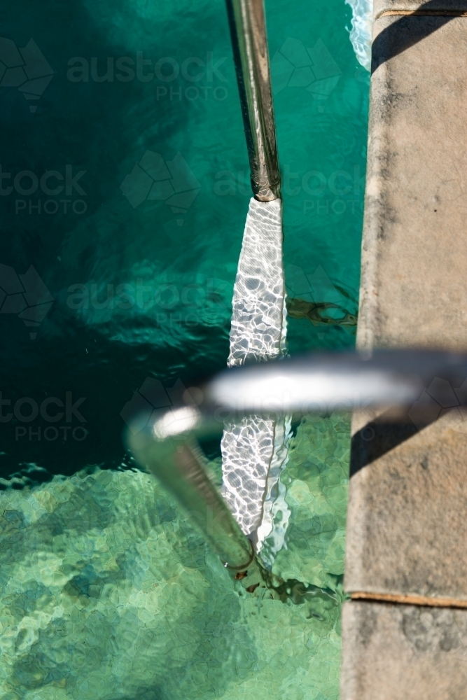 looking down at a ladder in a swimming pool - Australian Stock Image