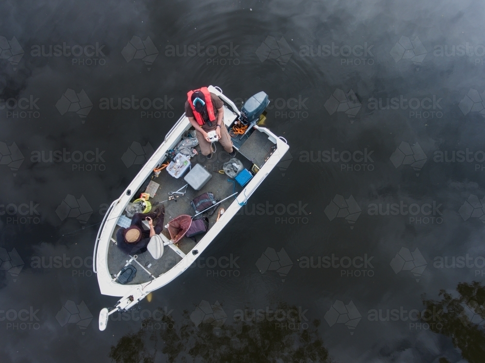 Looking down at Two Fishermen in a Messy Boat - Australian Stock Image