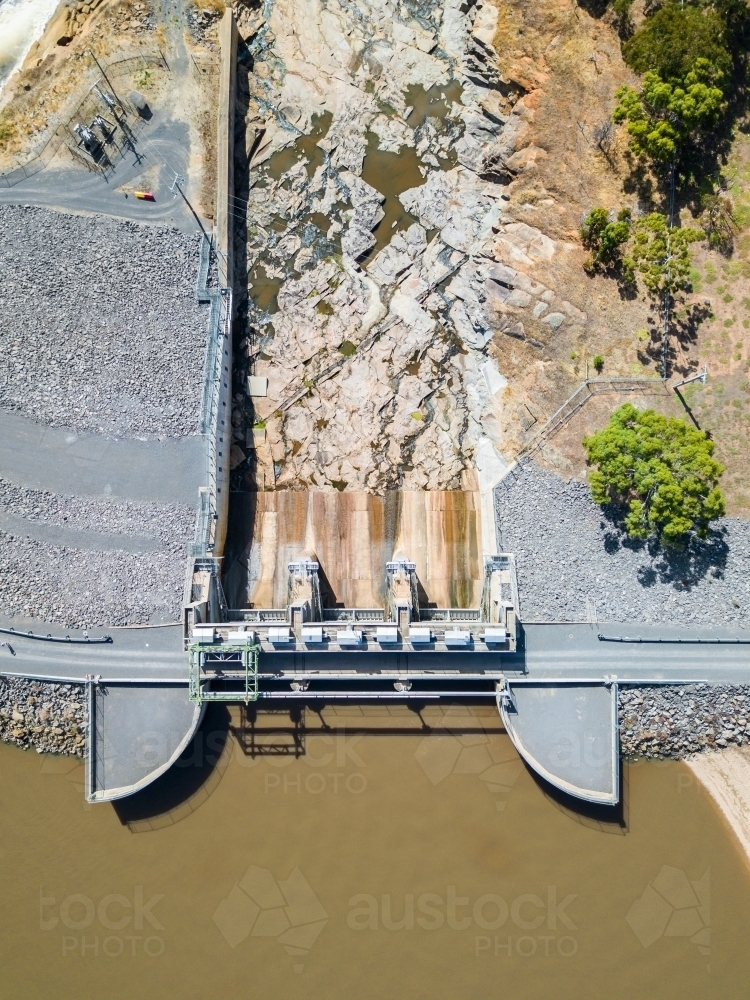 Looking down over the gates and dam wall of a water reservoir - Australian Stock Image