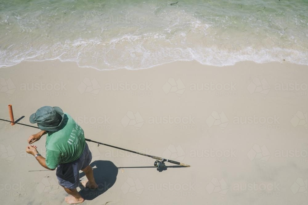 looking from above a fisherman preparing his line with bait - Australian Stock Image