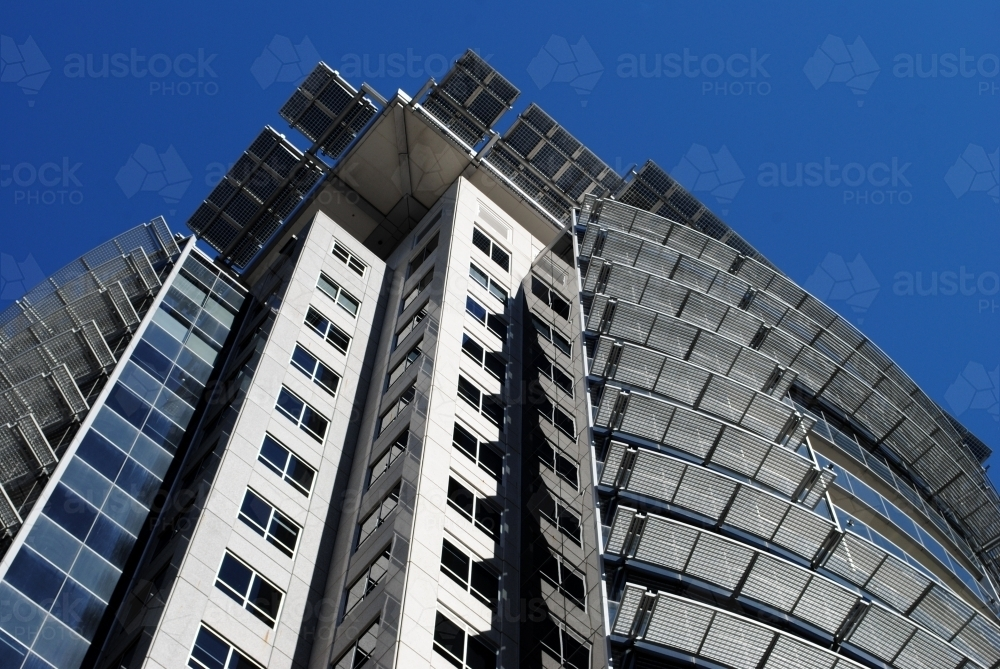 looking up at a modern office building against blue sky - Australian Stock Image