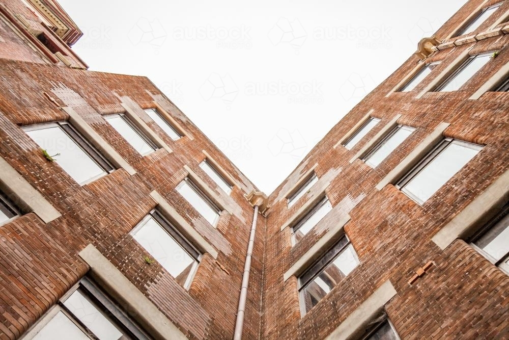 Looking up at old brick city buildings on overcast day - Australian Stock Image
