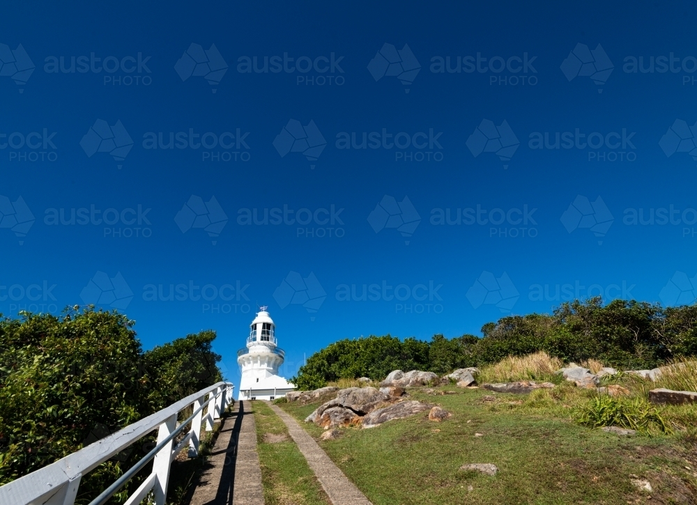 Looking up path to white lighthouse with deep blue sky - Australian Stock Image