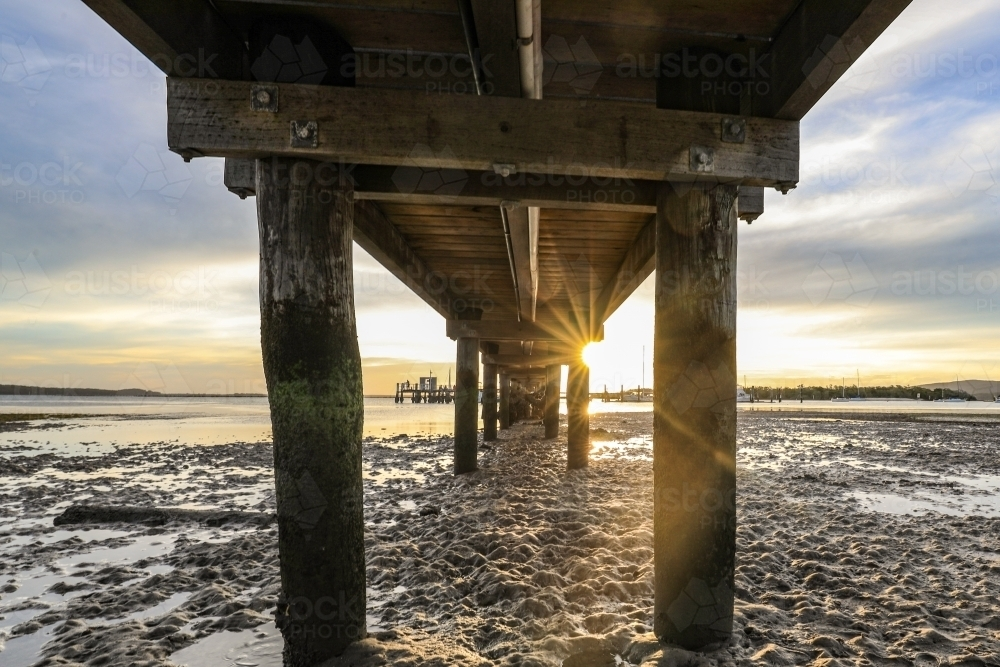 Low angle view of timber jetty leading to sunset through pylons - Australian Stock Image
