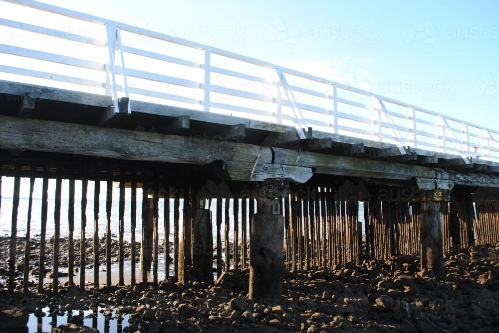 Low view of wooden pier at low tide - Australian Stock Image