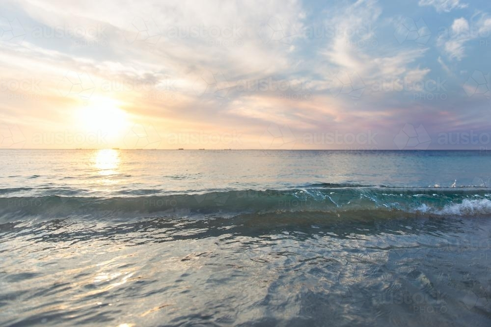 Low waves and pretty colours at the beach at sunset in summer - Australian Stock Image