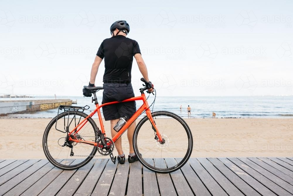 Male bike rider leaning against bike viewing the beach - Australian Stock Image