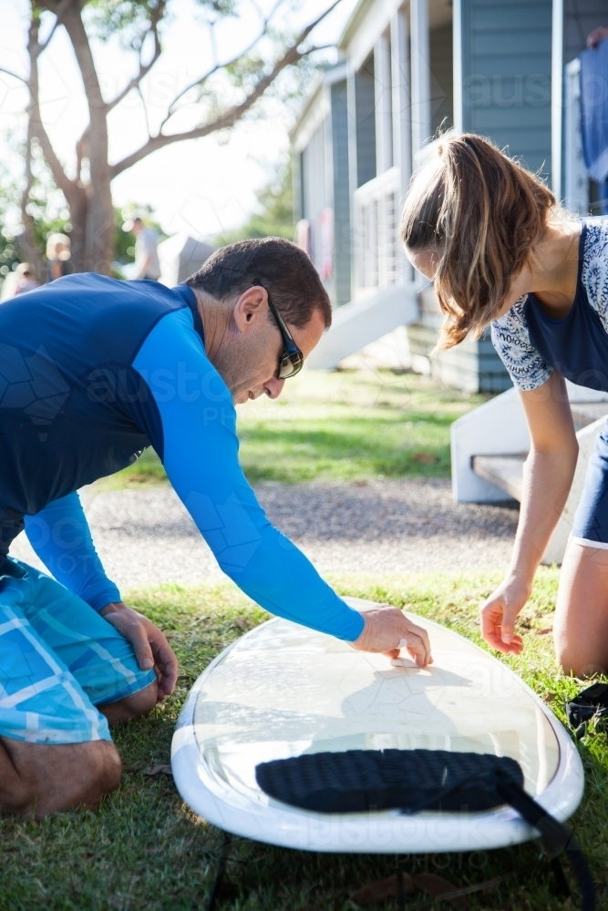 Male surfer waxing new surfboard with wax teen daughter watching - Australian Stock Image
