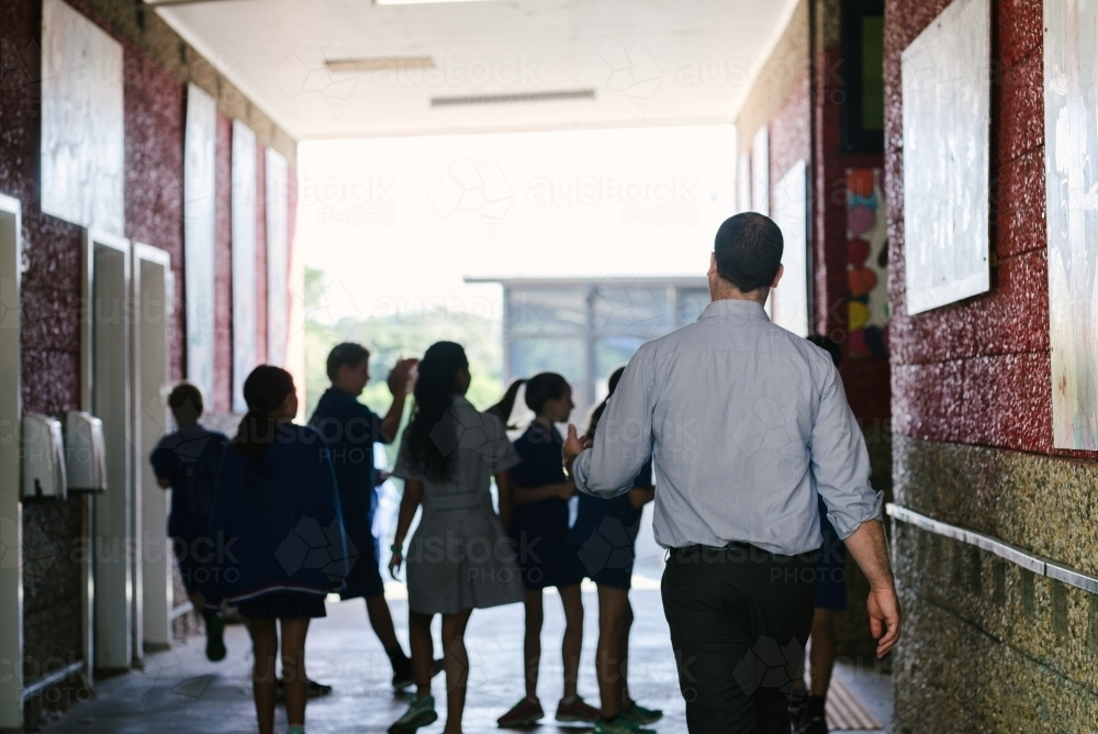Male teacher following primary students down a school hall - Australian Stock Image