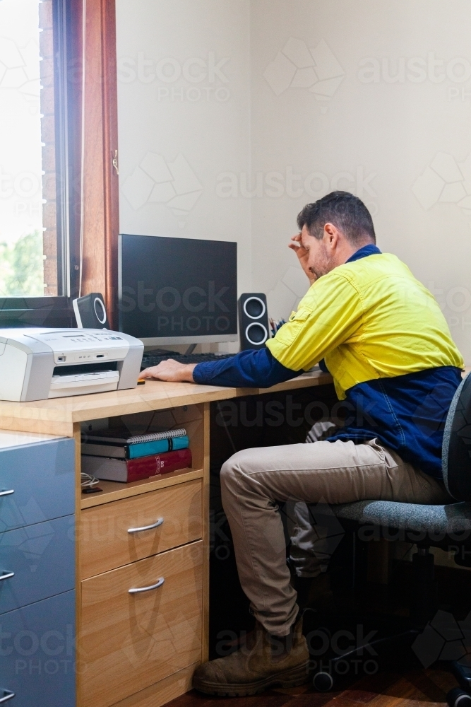 Male tradie at home office desk feeling overwhelmed and exhausted - Australian Stock Image