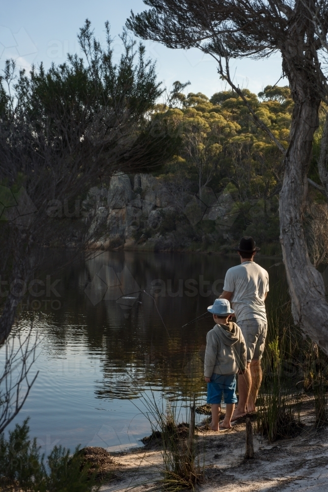Man and boy fishing at river outlet with sun ray light - Australian Stock Image