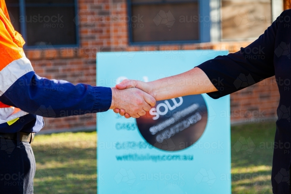 Man and businesswoman shake hands in front of house sold sign - Australian Stock Image